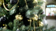 Golden balls and chains. New Year's and abstract blurred shopping mall background with Christmas tree decorations video