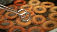 Golden crispy onion rings frying in a pan video
