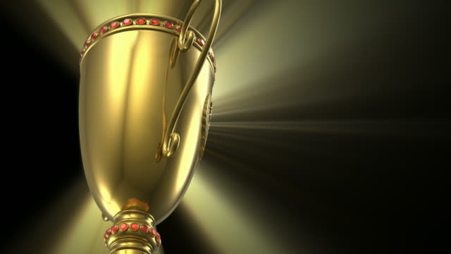 Golden glowing trophy cup on black background video