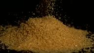 Golden sugar pouring on black background video