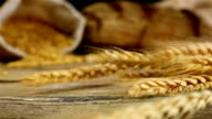 Golden wheat stems falling on the old wooden background, slow motion video