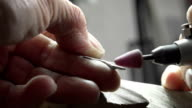 Goldsmith is polishing a silver cross with a polishing machine video