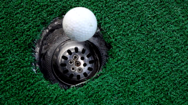 Golf ball rolling into the hole on putting green,Slow motion video