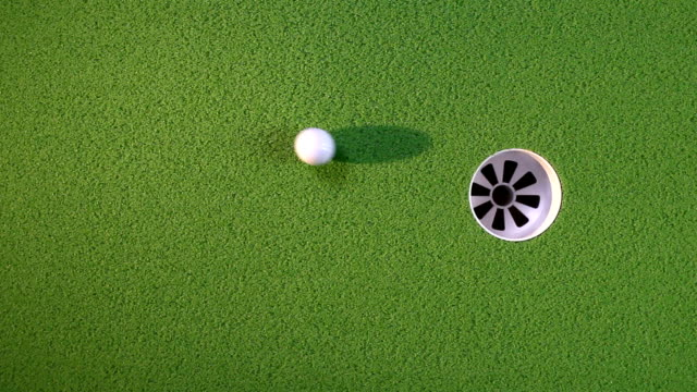 Golf balls curl into cup video