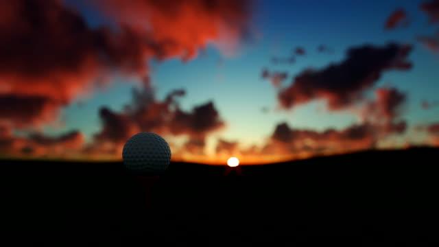 Golfball on tee against beautiful timelapse sunrise video