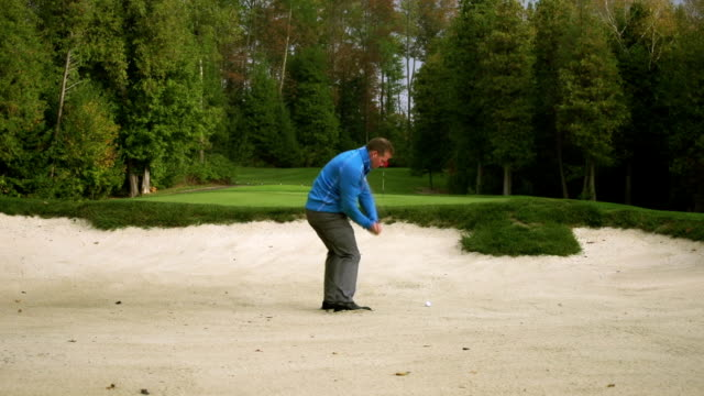 Golfer chips ball from Sand Trap video
