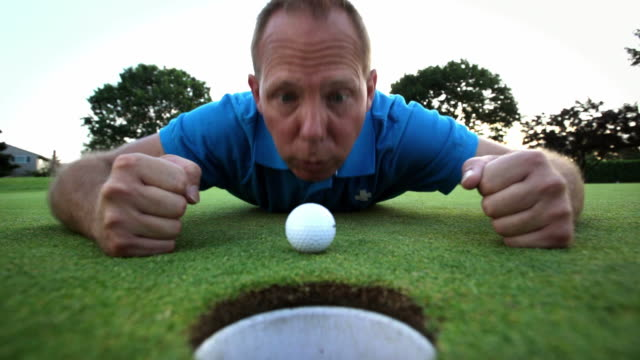 Golfer laying down stairs at his ball. video