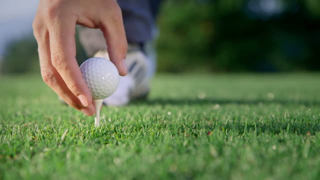 Golfer putting a ball on a tee video
