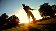 SLO MO WS PAN Golfer Teeing Off At Sunset video