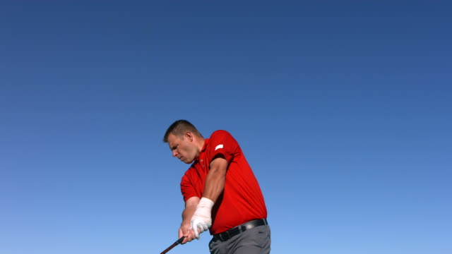 Golfer tees off, slow motion video