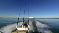 Gone fishing! Motor boat view looking back towards cargo ship. video