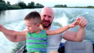 good dad at the weekend with the child, Father and son spend time together, emotionally respond during fast driving on a speed boat video