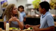 Good friends talking in school cafeteria video