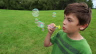 Good looking boy blows bubbles video