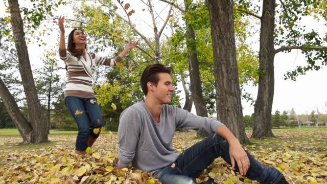 Good looking girl throws leaves on boyfriend. video