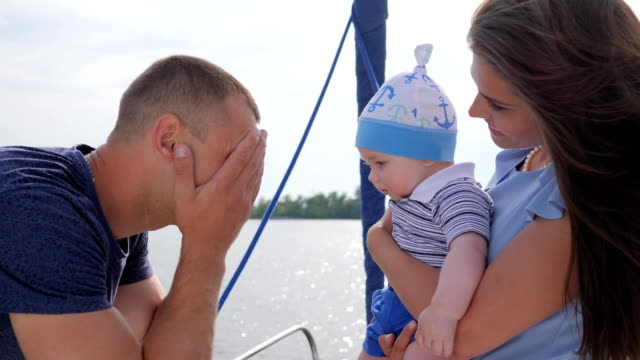 good mood of friendly family on vacation to river, young mom and dad played with baby on sea in boat video