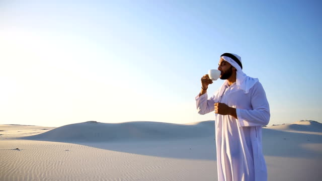 Good morning for male sheikh in middle of huge desert over cup of coffee against blue sky and dunes in open air video
