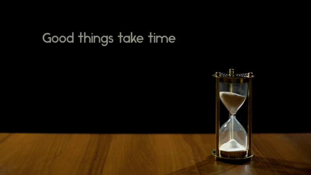 Good things take time, popular expression about patience, sandglass on table video