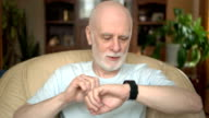 Good-looking handsome smiling senior man sitting in chair at home. Using smartwatch, sending message video