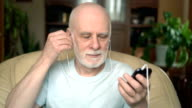 Good-looking senior man sitting in chair at home. Listening music on smartphone with ear-phones video