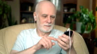 Good-looking senior man sitting on chair at home. Listening music on smartphone with ear-phones, singing video