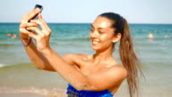 Gorgeous girl taking selfies on the beach video