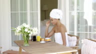 Gorgeous woman wrapped in towel sitting at table video