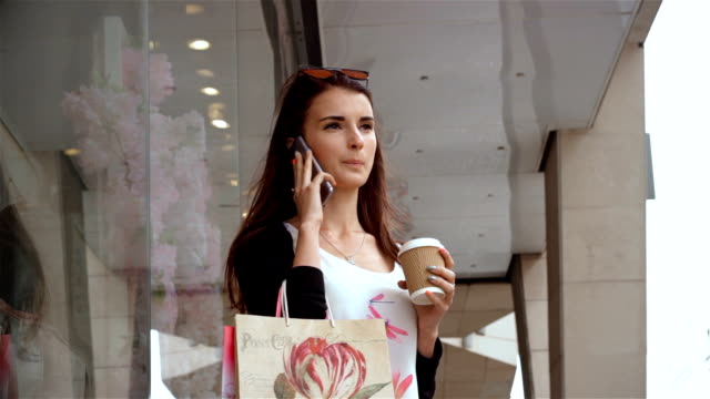 gorgeous young girl with packages worth near the shop and talking on the phone video