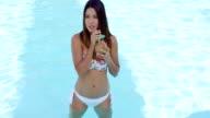 Gorgeous young woman in bikini at pool video