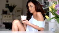 Gorgeous young woman sitting drinking coffee video