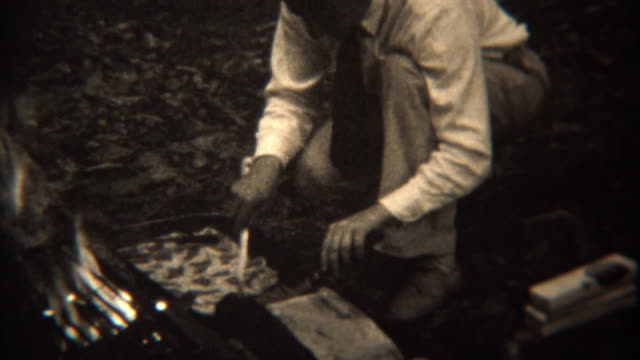 1937: Gourmet campfire cooking grilling pastries frying food. video