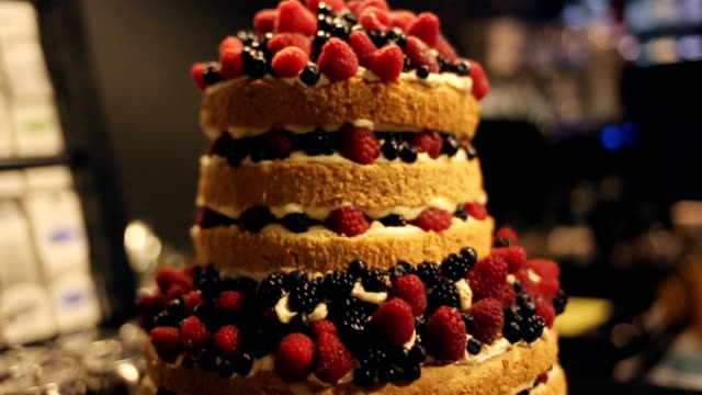 Gourmet tiered wedding cake decorated with berries at wedding reception. video