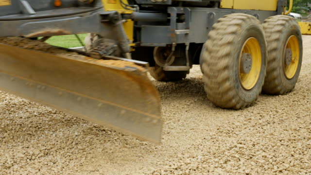 Grader excavator spread the crushed stone on the road video