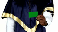 Graduate holds a green card. White. Close up video