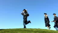 Graduates running over hill, slow motion video