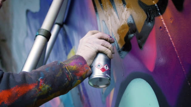 Graffiti artist painting on the wall, exterior, close up video