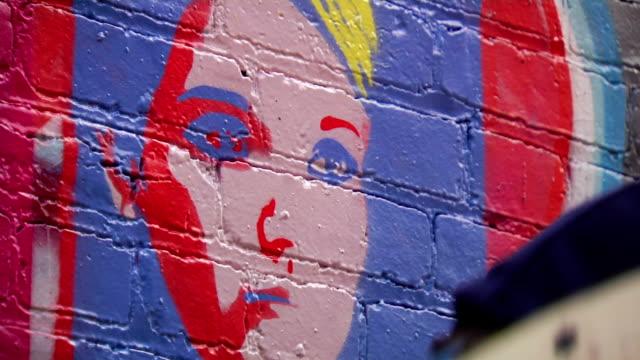 Graffiti Artist Removes Stencil from Wall Art - CU video