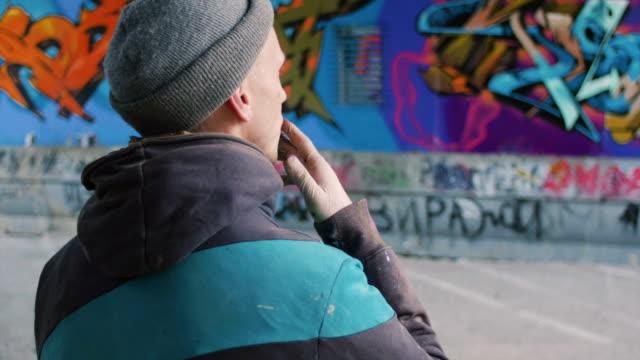 Graffiti artist smoking cigarette and watching at his work video