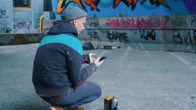 Graffiti artist using smartphone at graffiti background video