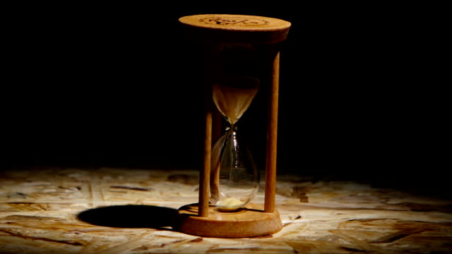 Grains of sand fall down in the hourglass. Spot light video