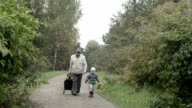 Grandad and grandson walking. video