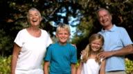 Grandchildren and grandparents posing in a park video