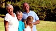 Grandchildren and grandparents standing in a park video