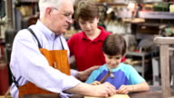 Grandchildren in workshop with grandfather reparing antique furniture. video