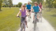 SLO MO Grandchildren riding bikes with grandparents video