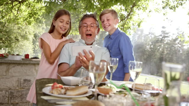 SLO MO Granddad making a selfie with his grandkids at the picnic table video