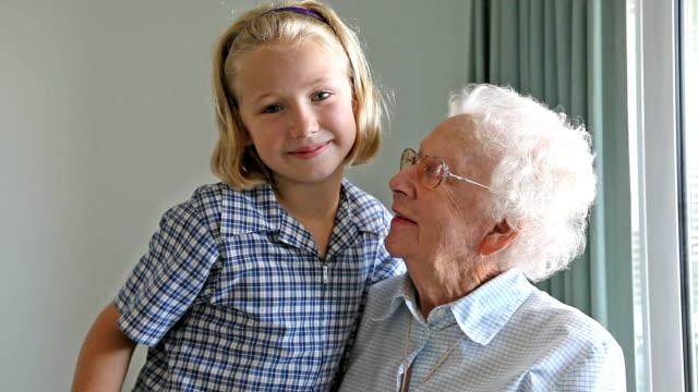 Granddaughter giving her Grandmother a hug indoors video