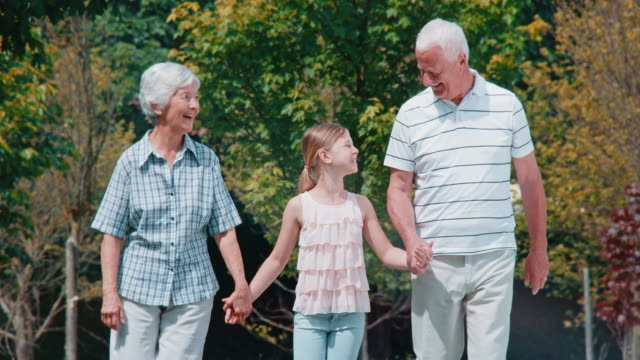 SLO MO Granddaughter holding hands with grandparents on their walk video