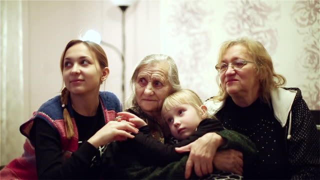 Granddaughter, mother, grandmother and great-grandmother sitting together on the bed. video