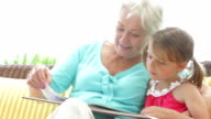 Granddaughter Reading Book With Grandmother video